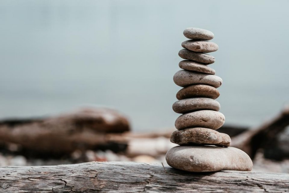 rock-stack-on-log-by-water_925x
